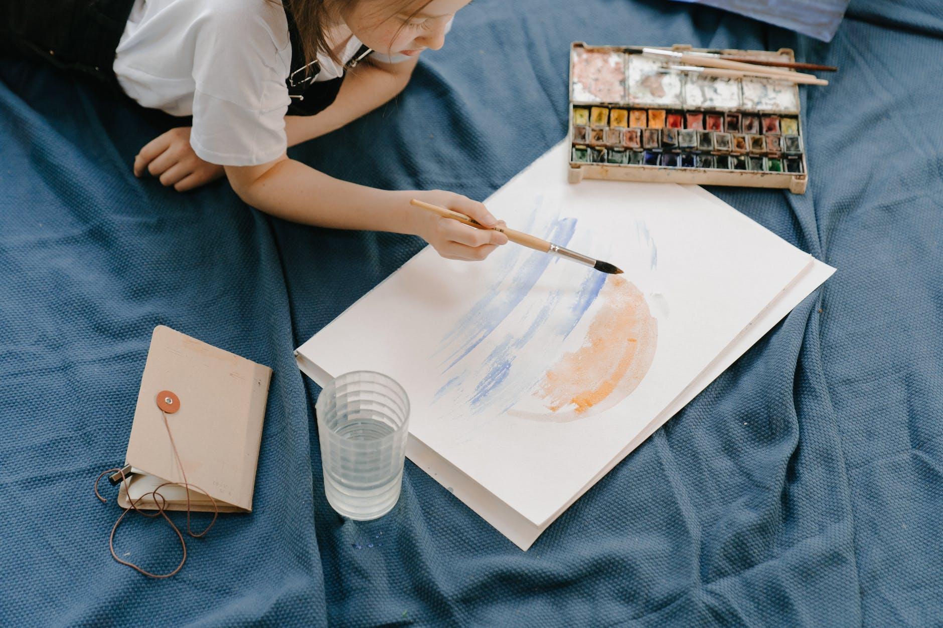 girl in white shirt holding paint brush